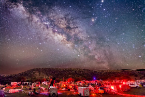 The galactic centre region of the Milky Way in Sagittarius and Scorpius, over the upper field of the Texas Star Party, near Fort Davis, Texas, May 13, 2015. About 600 people gather here each spring for a star party under very dark skies near the MacDonald Observatory. Sagittarius is left of centre and Scorpius is right of centre with the planet Saturn the bright object at the top edge right of centre. The dark lanes of the Dark Horse and Pipe Nebula areas lead from the Milky Way to the stars of Scorpius, including Antares. The semi-circular Corona Australis is just clearing the hilltop at left of centre. This is a composite of 5 x 3 minute exposures with the camera tracking the sky for more detail in the Milky Way without trailing. Each tracked exposure was at ISO 1600. The ground comes from 3 x 1.5-minute exposures at ISO 3200 taken immediately after the tracked exposures but with the drive turned off on the tracker. All are with the 24mm lens at f/2.8 and filter-modified Canon 5D MkII camera. The ground and sky layers were stacked and layered in Photoshop. The tracker was the Sky-Watcher Star Adventurer. High haze added the natural glows around the stars — no filter was employed here.